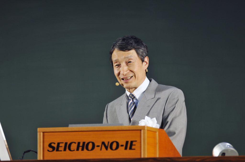 Supremo Presidente da Seicho-No-Ie, Professor Masanobu Taniguchi falando ao microfone e sorrindo